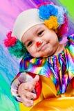 Een aardig jong geitje dat clownkleren draagt. Stock Foto