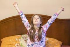 Een aardig kindmeisje geniet van zonnige ochtend Goedemorgen thuis Het kielzog van het kindmeisje omhoog van slaap Meisje het uit royalty-vrije stock afbeeldingen
