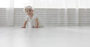 Een aardig meisje in een verband en een kleding die op de witte vloer kruipen stock footage