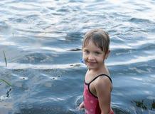 Een aardig oud meisje van vier jaar bevindt zich glimlachend en lachend in het open water royalty-vrije stock foto's