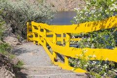 Een aardige gele omheining langs de stappen tegen de achtergrond van meer binnen royalty-vrije stock foto