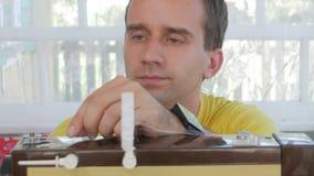 Een aardige mens zit thuis bij de elektrische naaimachine Hij naait verscheidene lagen van stof en dient een werkend hulpmiddel stock video