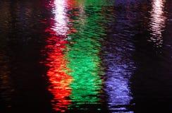 Een abstract beeld van vage rode, blauwe en groene lichten die tegen water nadenken Royalty-vrije Stock Afbeelding