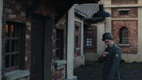 Een achterclose-up van een Duitse militair die een bol in een straatlantaarn veranderen die over een deur in een oude rode bakste stock video