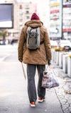 Een achtermening die van de dakloze bedelaarsmens die in openlucht in stad lopen, zak houden royalty-vrije stock afbeeldingen