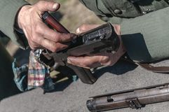 Een acteur die zich omhoog als Duitse militair kleden maakt zijn pistool schoon royalty-vrije stock fotografie