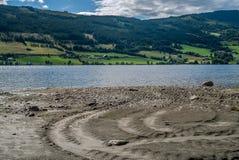 Een adembenemende landelijke panoramamening van landbouwbedrijven, bomen, meer en bergen van een ruw strand met zand en kiezelste stock fotografie