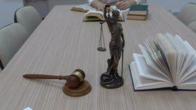 Een advocaat in de werkplaats onderzoekt documenten en de wetgeving, het beeldje van Themis met een algemeen plan stock videobeelden