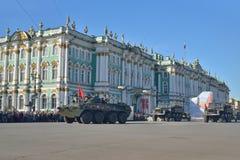 Een afdeling van infanterie op APC met een rode vlag en vrachtwagens  Stock Foto's