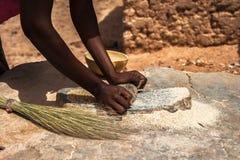 Een Afrikaanse gierst van vrouwen malende graangewassen Stock Afbeeldingen