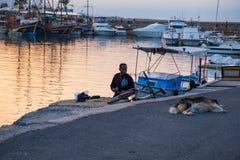 Een Afrikaanse mens bekijkt een hondslaap op het tarmac bij de oude haven van Kyrenia in Cyprus op een mooie middag stock fotografie