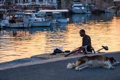 Een Afrikaanse mens bevindt zich door het overzees bij de oude haven van Kyrenia in Cyprus terwijl zijn hond op het tarmac slaapt stock fotografie