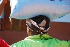 Een Afrikaanse vrouw die een zak suiker op het hoofd dragen Stock Afbeelding
