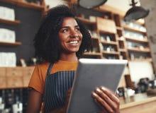 Een Afrikaanse vrouwelijke eigenaar die van koffie digitale tablet houden stock foto's