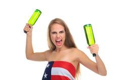 Een agressief die meisje, in een Amerikaanse vlag wordt verpakt, houdt twee groene flessen en boos schreeuwen Geïsoleerd op wit royalty-vrije stock afbeelding