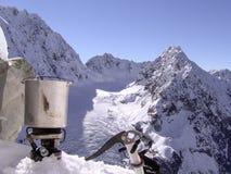 Een alpinist neemt een onderbreking om voedsel in de sneeuw te koken stock foto