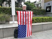 Een Amerikaanse mens toont de Amerikaanse vlag met de woorden` TROEF ONZE TRAGEDIE IS ` Op de Draadloze weg dichtbij de ambassade Stock Foto