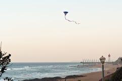 Een Amerikaanse Vlagvlieger vliegt over het strand bij Umhlanga-Rotsen, met de Millenniumpijler en de vuurtoren op de achtergrond Royalty-vrije Stock Afbeeldingen