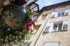 Een antieke die straatlantaarn met bloemen wordt verfraaid Stock Afbeelding