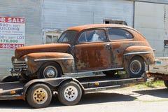 Een antieke Ford-sedan op een aanhangwagen voor verkoop Stock Fotografie