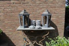 Een antieke grijze lijst met lantaarns en kaarsenhouders tegen een muurclose-up in een tuin in de zomer stock afbeelding
