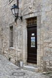 Een antieke houten deur, een ijzerlantaarn en een beeldhouwwerk Pietà boven de deur stock afbeeldingen