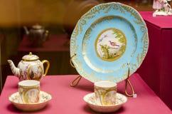 Een antieke reeks ceramische theepotten, koppen, schotels op een houten lijst stock afbeelding