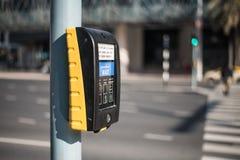 Een apparaat met een knoop van de verkeerslichtcontrole voor voetgangers toont een rood en twee groene mensen stock afbeelding