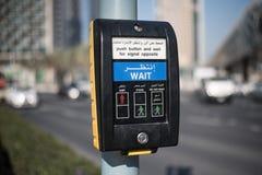 Een apparaat met een knoop van de verkeerslichtcontrole voor voetgangers toont een rood en twee groene mensen stock afbeeldingen