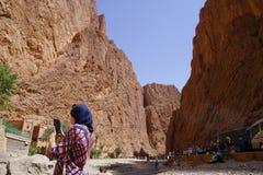 Een Arabische die vrouw met haar telefoon in de rivier van de Todra-kloven in Marokko wordt gefotografeerd Royalty-vrije Stock Afbeeldingen