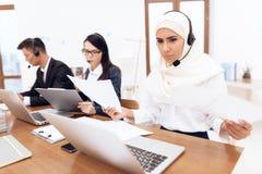 Een Arabische vrouw werkt in een call centre stock foto's