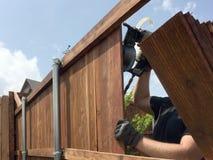 Een arbeider bouwt een aardige omheining royalty-vrije stock afbeelding