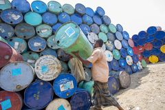 Een arbeider hijst een leeg vat olie boven zijn hoofd bij Sadarghat-gebieden, Chitagong, Bangladesh Stock Foto