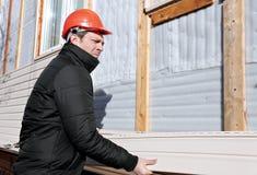 Een arbeider installeert panelen het beige opruimen op de voorgevel Stock Afbeelding