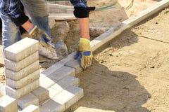 Een arbeider legt het bedekken plakken langs een concreet blok op een voorbereide vlakke zandige oppervlakte op de bestrating royalty-vrije stock afbeelding