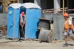 Een arbeider maakt ecologische toiletten op een bouwwerf leeg Stock Fotografie