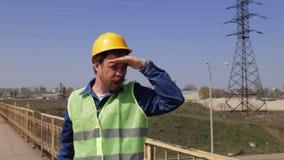 Een arbeider met een baard en een snor in een gele helm bevindt zich op de brug en onderzoekt de afstand die zijn hand houden dic stock videobeelden