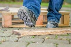 Een arbeider met de stappen van veiligheidsschoenen op een spijker Stock Foto