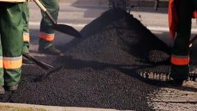 Een arbeider nivelleert misvormingen met koud asfalt op een landelijke weg stock footage