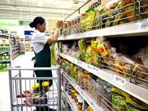 Een arbeider van de kruidenierswinkelopslag vult de planken met nieuwe voorraden van verschillende soorten voedsel opnieuw royalty-vrije stock afbeeldingen
