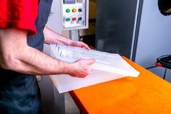 Een arbeider verzegelt de vorm voor het gieten van plastiek Productie van plastic producten Middelgroot bedrijfsconcept Het proce stock fotografie