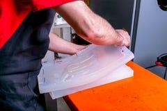 Een arbeider verzegelt de vorm voor het gieten van plastiek Productie van plastic producten Middelgroot bedrijfsconcept Het proce stock foto's
