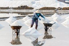 Een arbeider vult kruiwagens bij de zoute gebieden van Hon Khoi in Nha T Royalty-vrije Stock Afbeelding