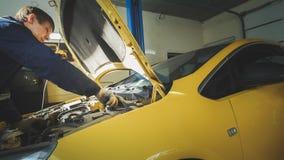 Een arbeiderswerktuigkundige controleert elektro in de kap van de gele auto, garageworkshop Stock Fotografie