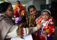 Een arts controleert een mooie meisjezitting op haar moedersoverlapping stock afbeelding