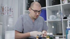 Een arts die in glazen bij de lijst zitten zet op rubberhandschoenen Farmacologie en geneeskundeconcept stock footage