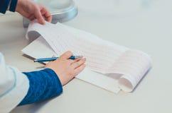 Een arts die het resultaat van een elektrocardiogram controleren en nota's maken stock foto