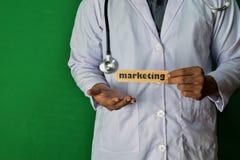 Een arts die, houdt de Marketing document tekst op Groene achtergrond bevinden zich Medisch en gezondheidszorgconcept stock foto