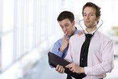 Een arts die laptop met een stethoscoop analyseert Stock Afbeelding