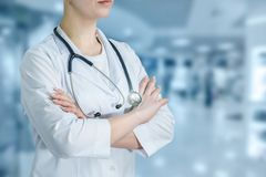 Een arts die zich in de het ziekenhuiszaal bevinden met gekruiste handen royalty-vrije stock foto